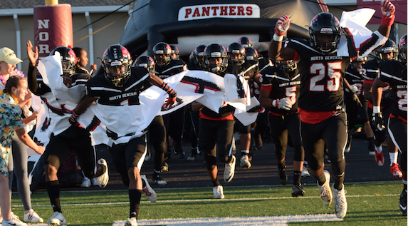The football team beat Fishers last year. The team runs out on to the field.