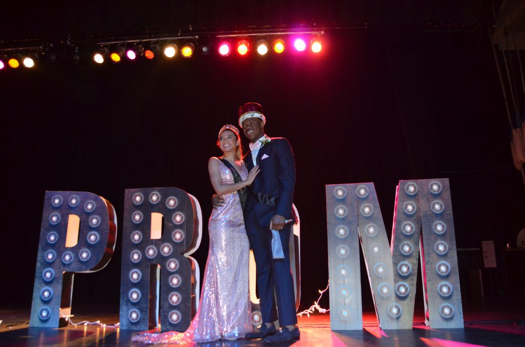 The Prom king and queen of 2019 pose in front of the Prom sign. The 2020 and 2021 Proms were both cancelled due to COVID-19.