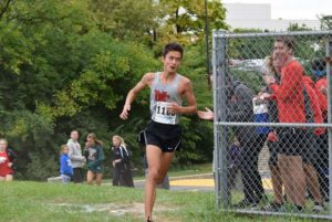 A student runs in the state cross country tournament. Taylor Marshall is the head boys track and cross country coach.