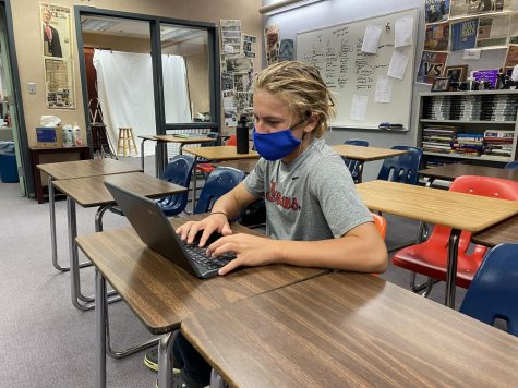 Freshman Eli Thompson works on his computer during class. Students are easily distracted by other applications on their computer, causing them to not learn the required material.