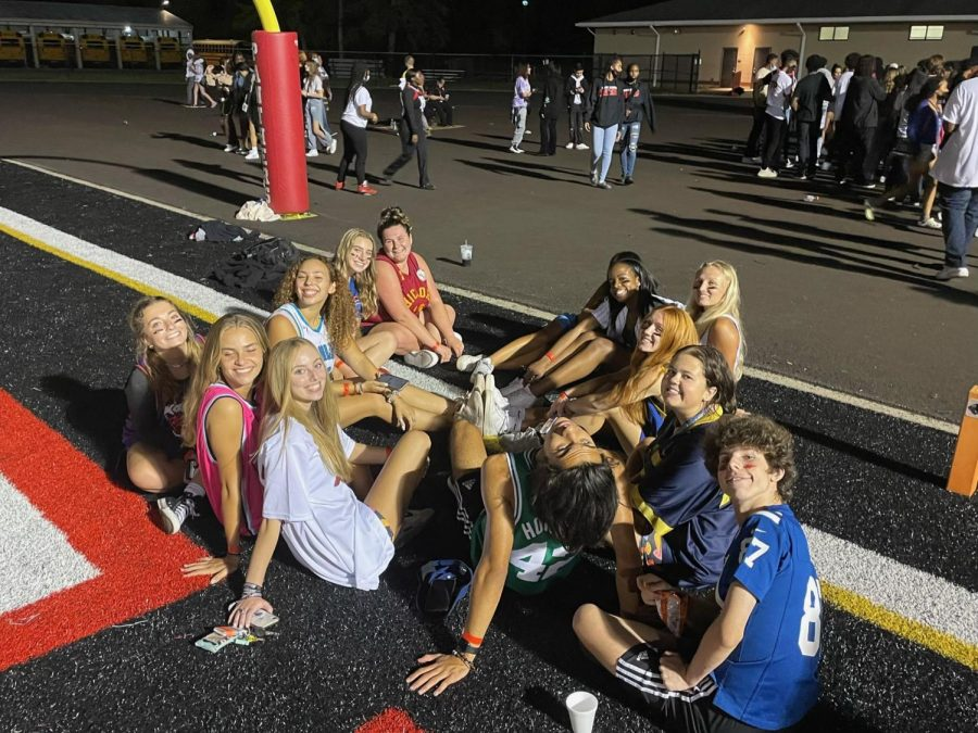 Students sit underneath the goalpost dressed in their jerseys. The student section theme that game was jerseys, so many students stayed in their jersey spirit wear from the earlier event.
