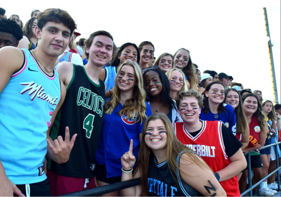 Student section cheers on the football team from the stands.  Each football game has a different theme for students to come dressed up as.