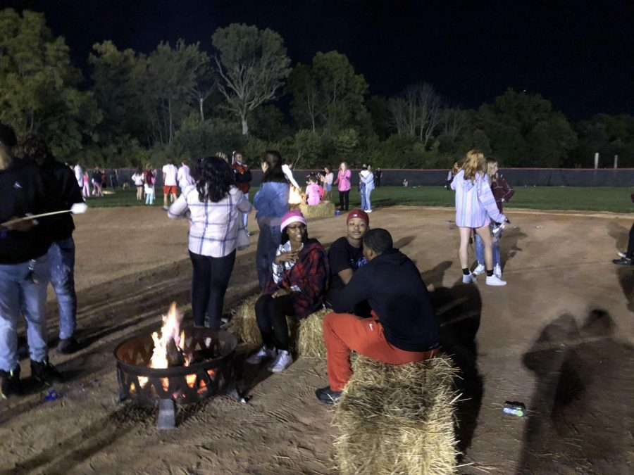 Students gather around a fire pit at the senior bonfire. Seniors were encouraged to dance, play games, make smores and hang out with friends at the gathering.